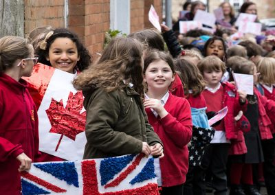 Smiling school children with flags in Church Street